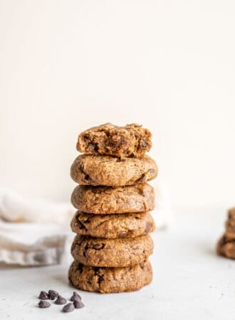 A stack of grain-free peanut butter cookies against a white surface.