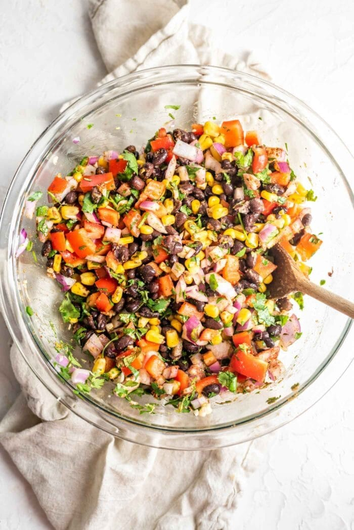 Southwest black bean corn salad in a large mixing bowl on a white surface.
