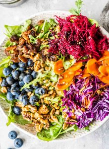 Salad with beet, carrot, walnuts, raisins, cabbage and blueberries.
