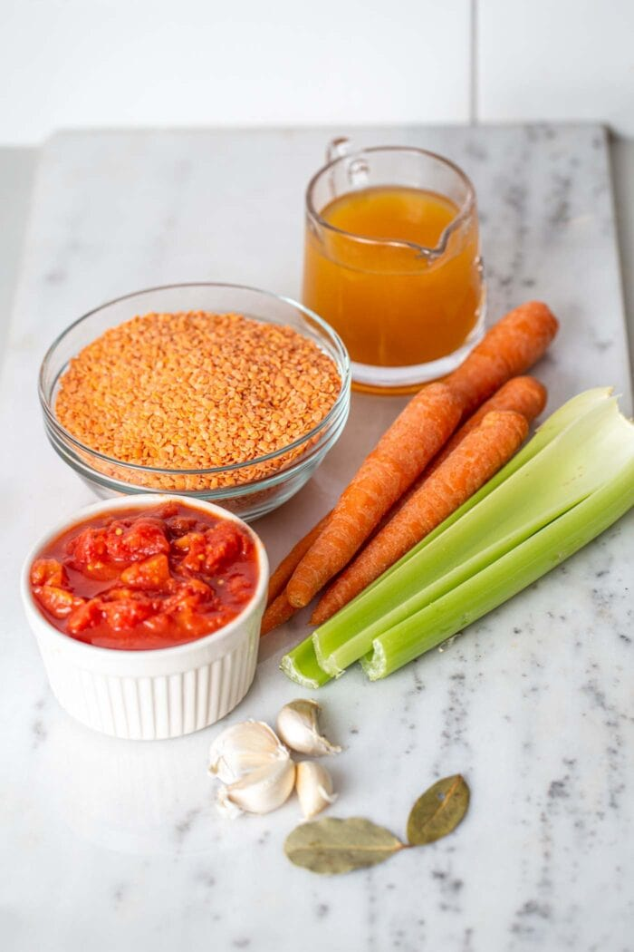 Diced tomatoes, lentils, broth, carrots, celery, garlic and bay leaves in containers on a marble counter top.
