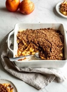 Grain-free vegan apple crisp being scooped out of a white baking dish.