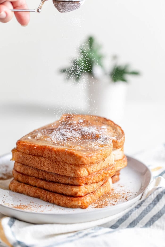 A stack of vegan french toast being sprinkled with powdered sugar.