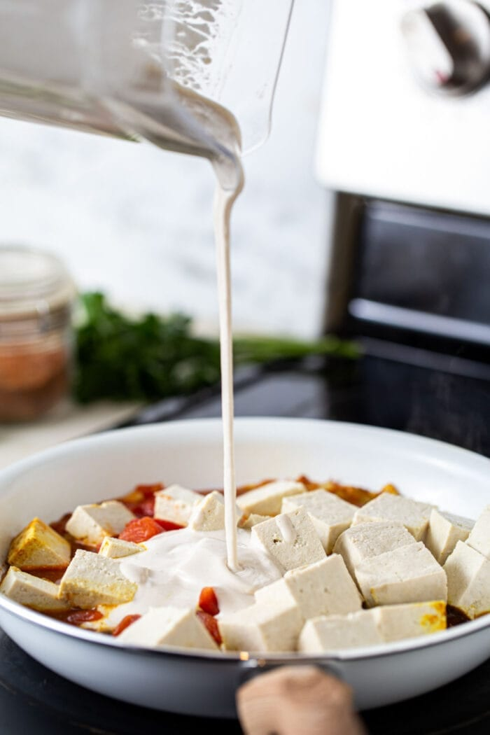 Cashew cream being poured from a blender into tofu butter chicken in a skillet on the stovetop.