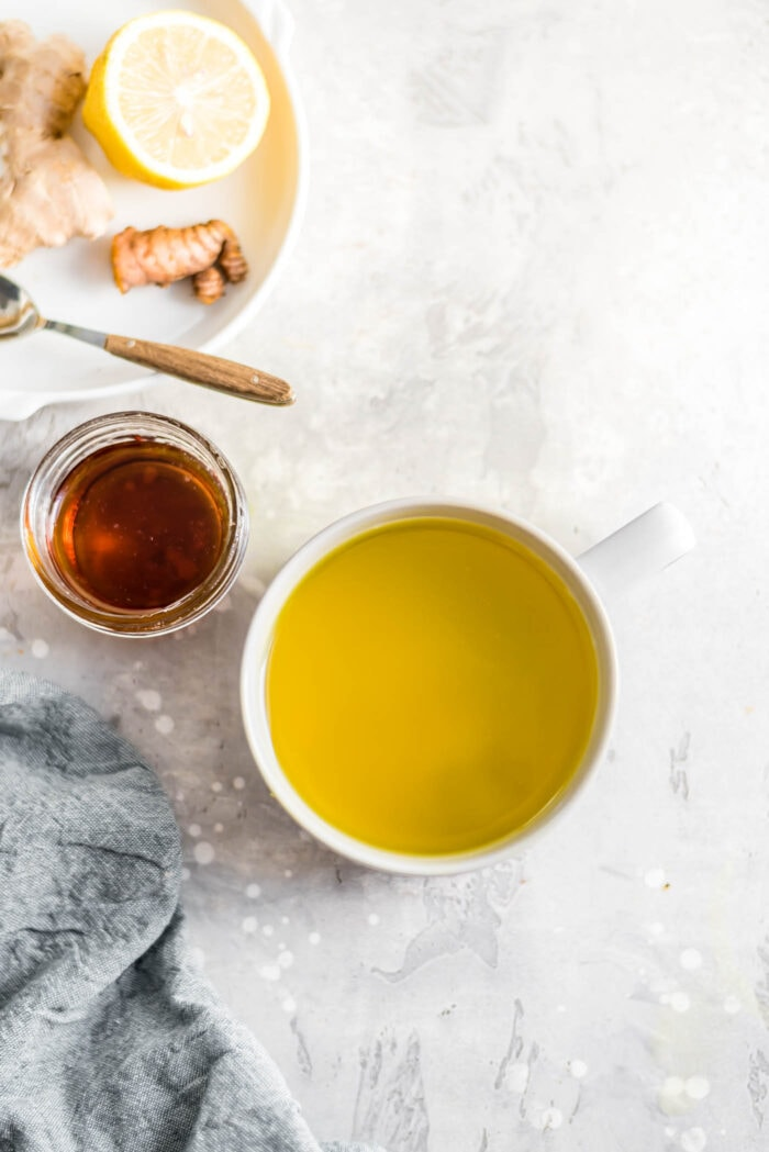 A mug of ginger turmeric tea with a small, glass jar of maple syrup and a sliced lemon beside it.