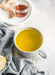 A grey mug of ginger turmeric tea and a small white dish with a container of maple syrup and fresh ginger and turmeric root sitting on it.