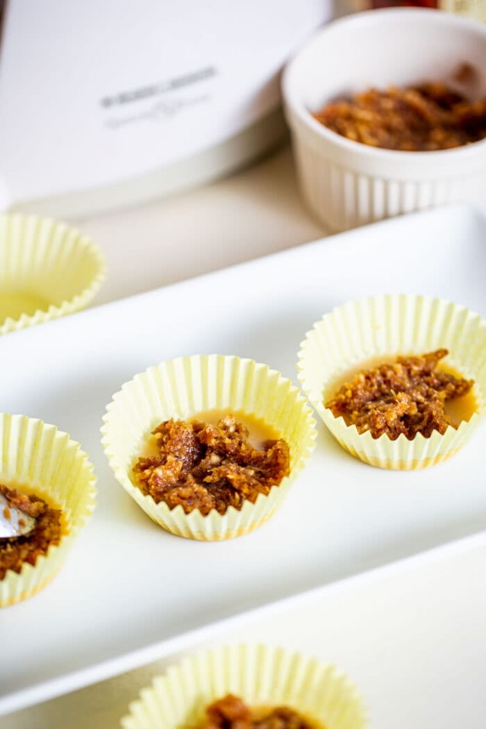 Date paste in 3 muffin liners on a small white plate.