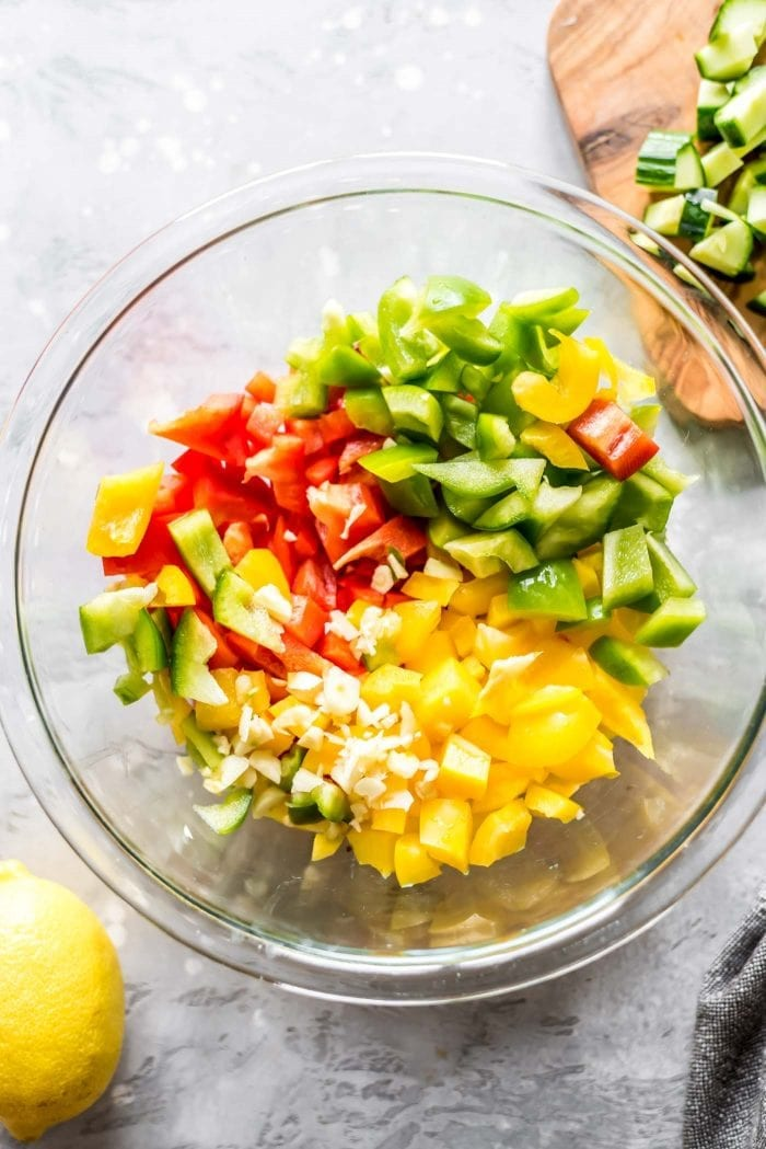 Diced yellow, red and green bell peppers in a large glass mixing bowl.