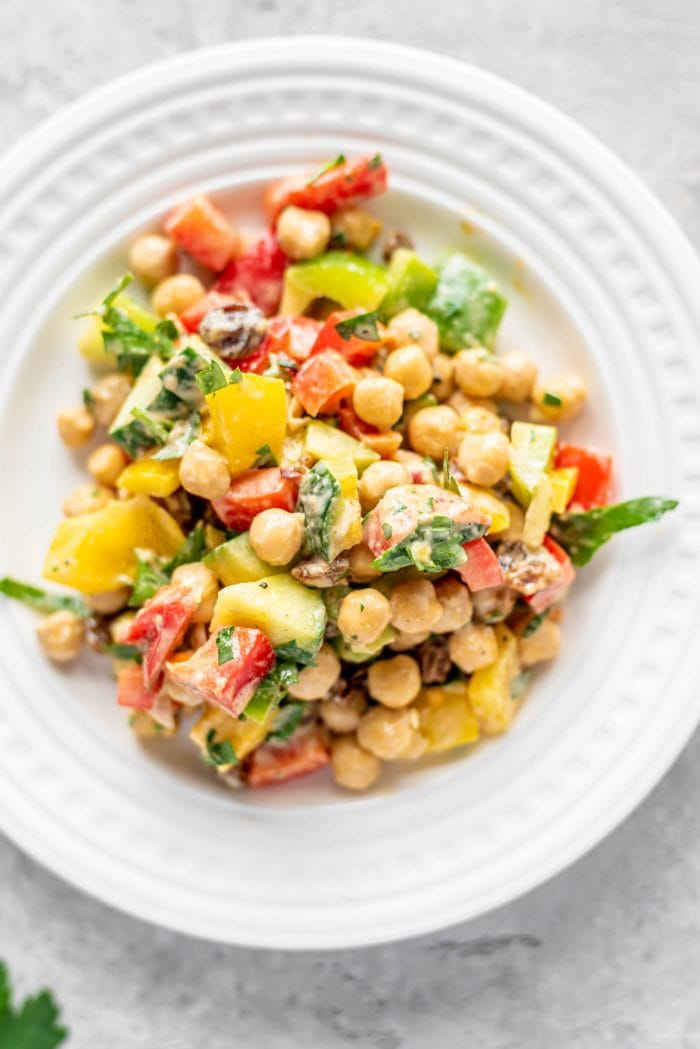 Chopped salad made with bell peppers, chickpeas and cucumber on a small white plate.