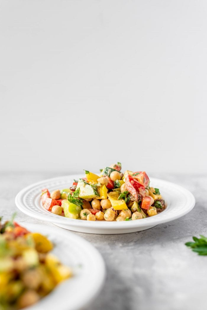 Bell pepper salad with raisins, tahini, chickpeas and cucumber on a white plate.