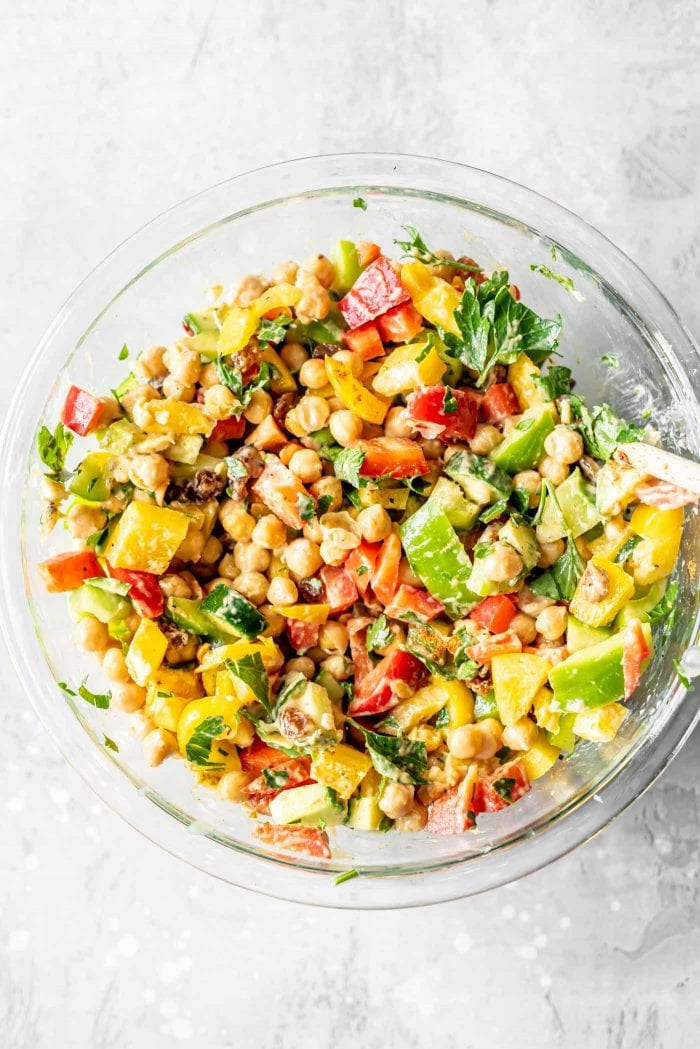 Diced bell peppers, chickpeas, raisins and tahini in a large glass mixing bowl.