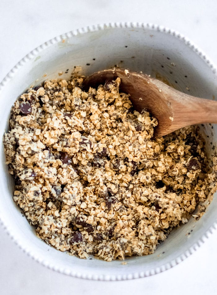 Chocolate chip oatmeal dough in a mixing bowl with a wooden spoon resting in bowl.