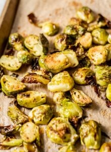 Maple dijon roasted brussel sprouts on a baking tray lined with parchment paper.