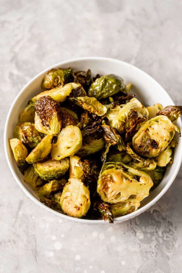 A small white bowl of maple roasted brussel sprouts.