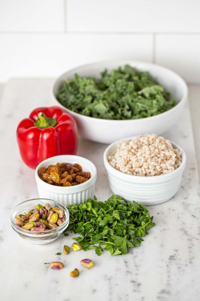 Pistachios, barley, bell peppers, kale and parsley in bowls on a countertop.