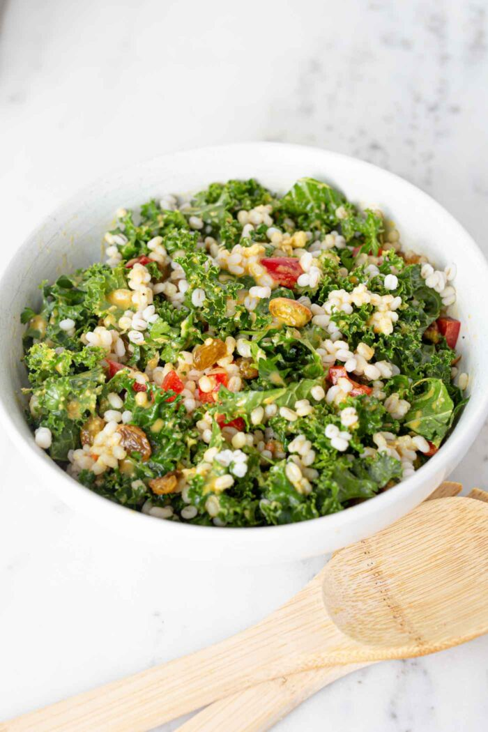 A colorful kale and barley salad with pistachios, bell peppers and raisins in a large salad bowl.