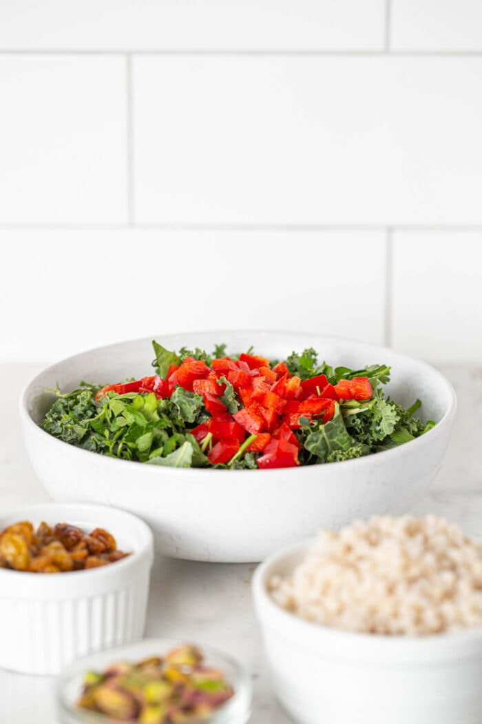 Kale and bell peppers in a large salad bowl.