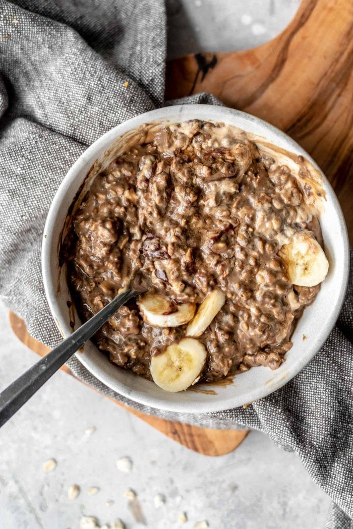 Bowl of vegan mocha protein oatmeal with banana and cashew butter.