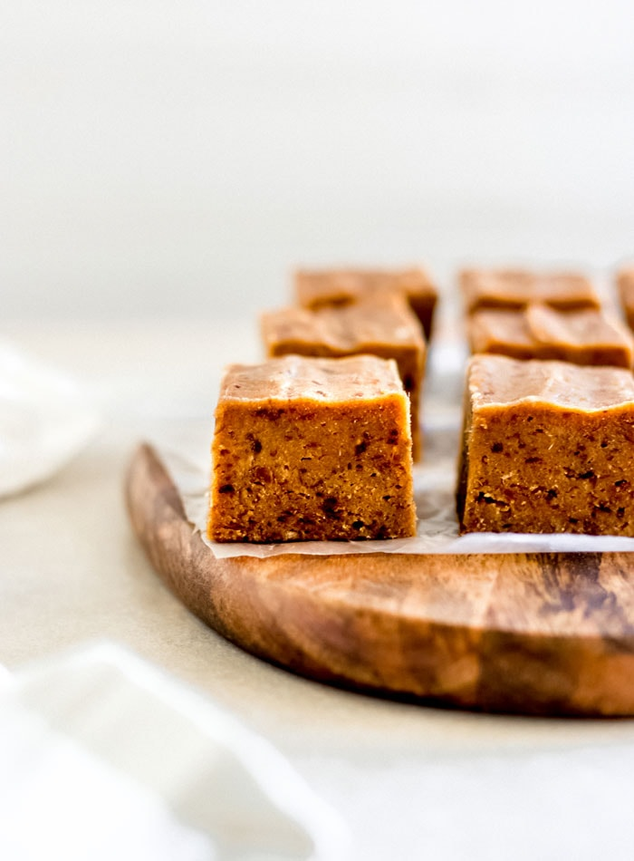 Cubes of pumpkin pie fudge sitting on parchment paper on a cutting board.