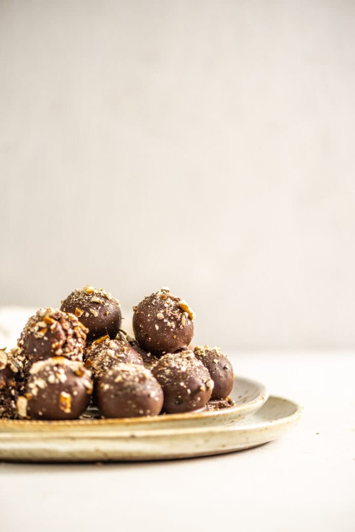 A plate full of chocolate covered truffles topped with crushed pretzels.