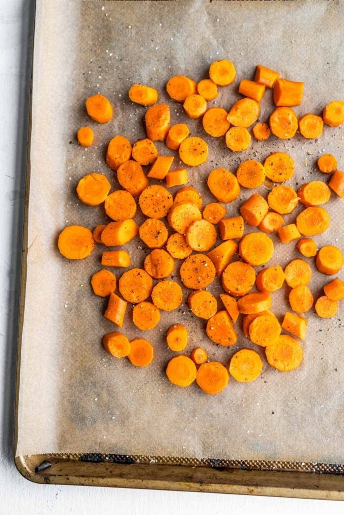 Chopped carrots sprinkled with salt and pepper on a parchment paper-lined baking tray.