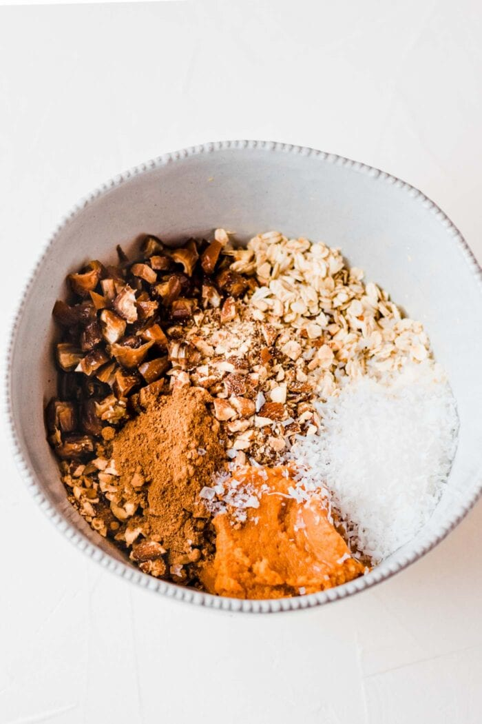 Oats, dates, pumpkin, coconut and spices in a mixing bowl.