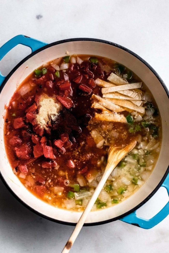 Garlic powder, diced tomatoes, garlic, onion, broth and jalepeno in a soup pot for making vegan tortilla soup.