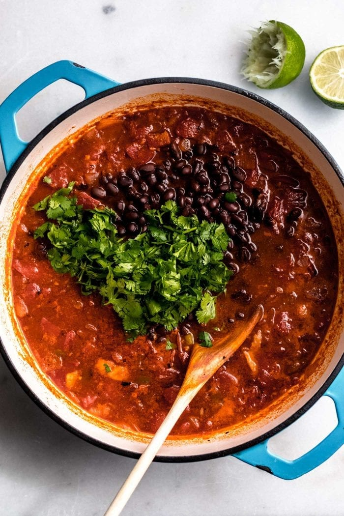 The best vegan tortilla soup in a pot topped with cilantro and black beans and a lime on the side.