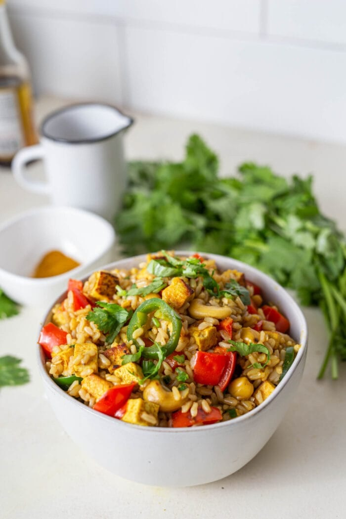 Cashew fried rice with tofu and veggies in a bowl with a fork.