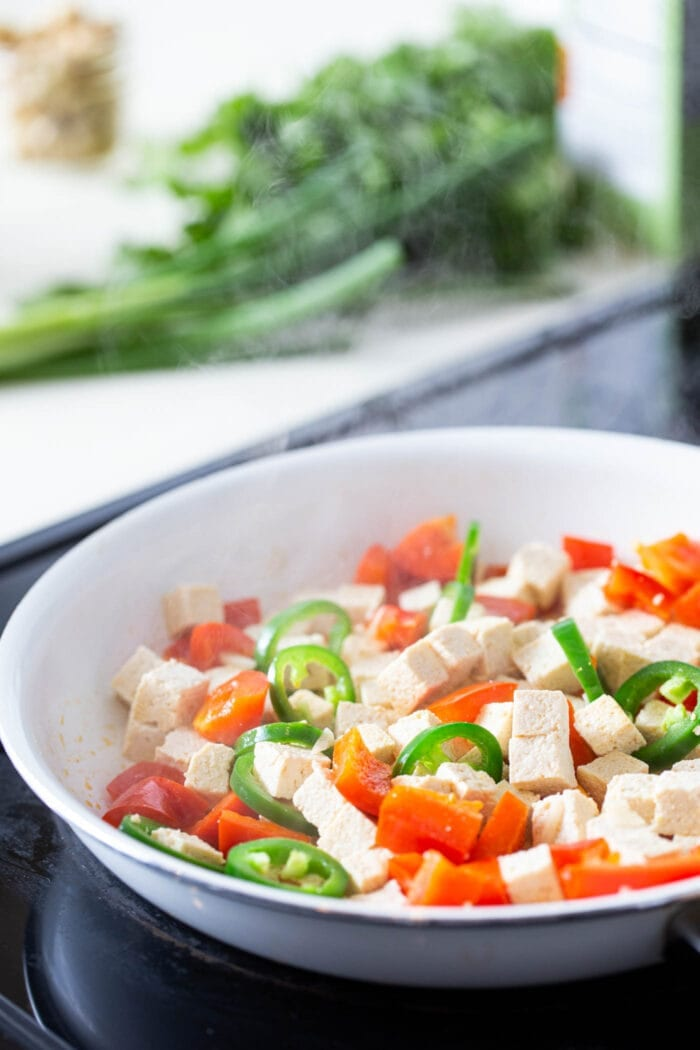 Tofu, bell peppers and jalapeno in a white skillet on the stovetop.