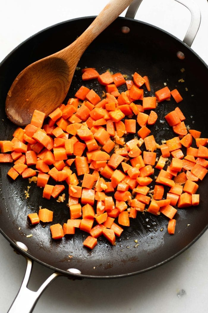 Diced carrots being cooked in a skillet to make fried cauliflower fried rice.