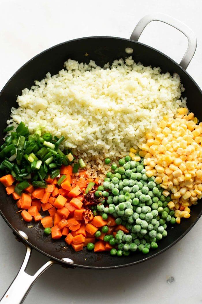 Riced cauliflower, carrots, peas, corn and green onion in a pan to make cauliflower fried rice.