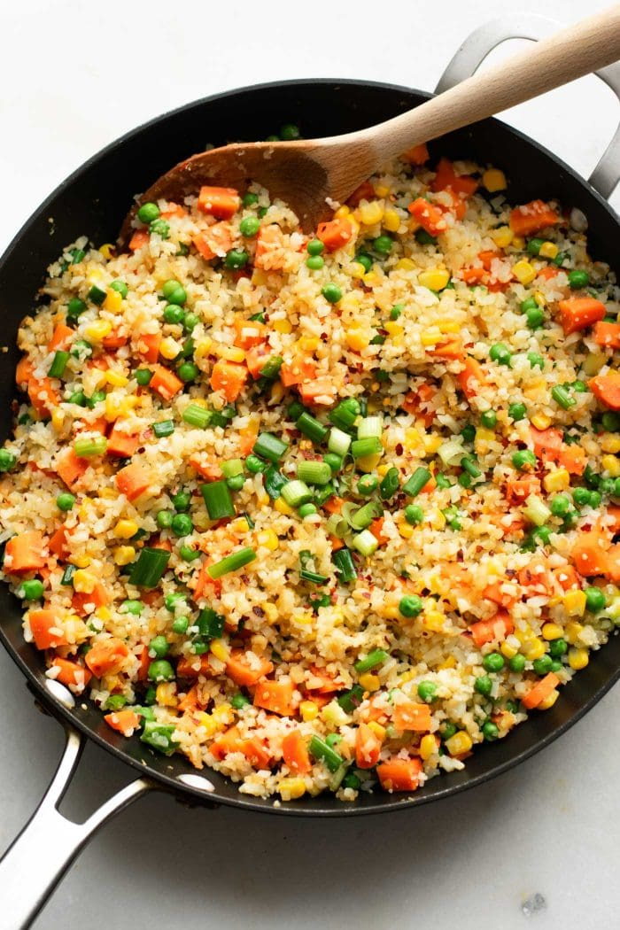 Cooked fried cauliflower rice in a pan with carrots, peas, corn and green onion.
