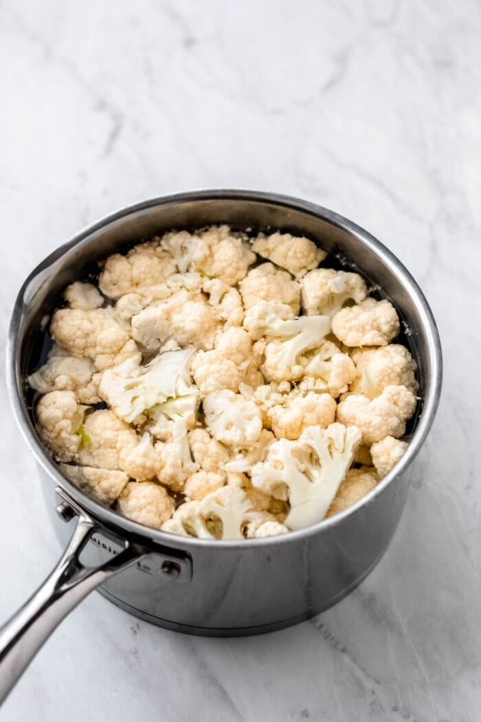 Raw cauliflower florets in a pot of boiling water.
