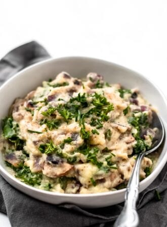 Close up of a bowl of mashed cauliflower with kale and mushrooms sitting on a grey napkin on a white surface.