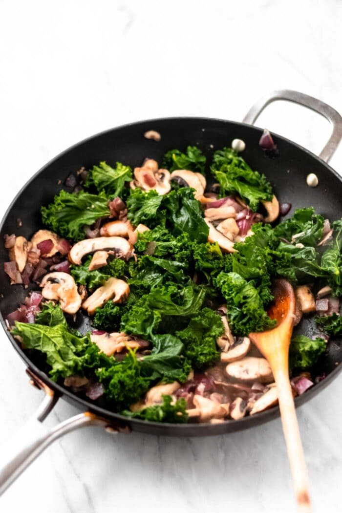 Cooked kale, mushrooms, onion and garlic in a pot with a wooden spoon.