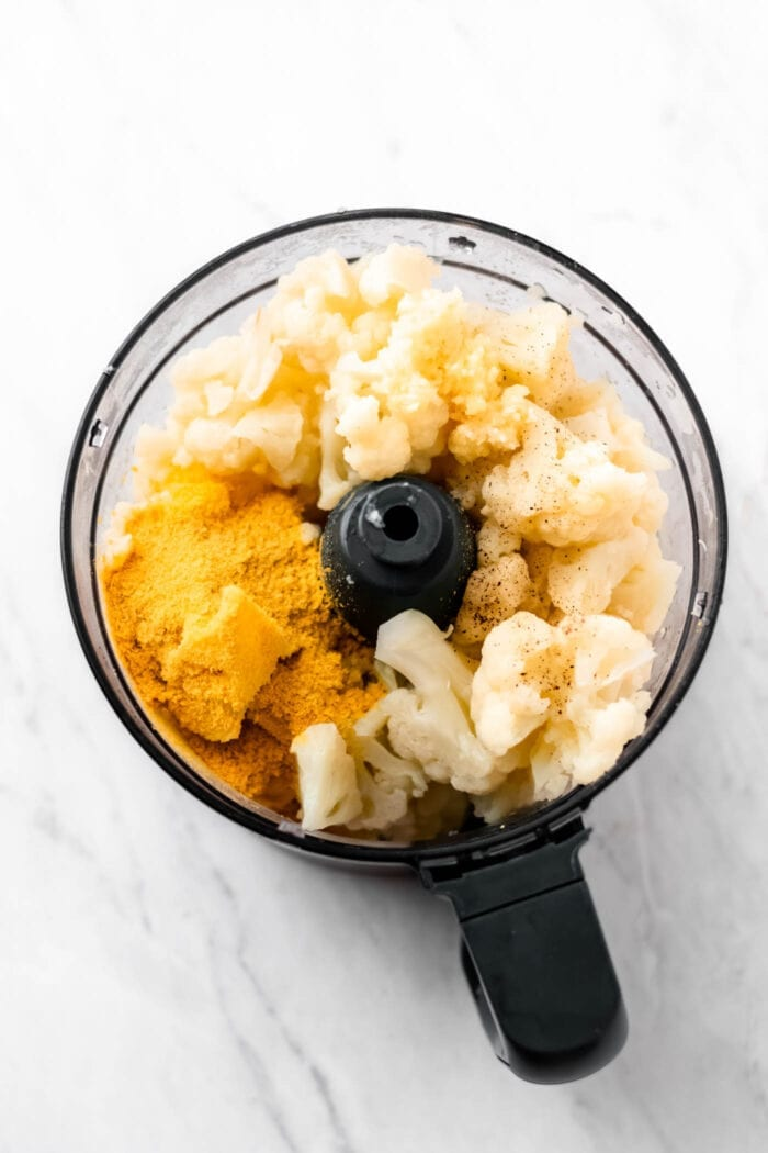Cooked cauliflower and nutritional yeast in a food processor.