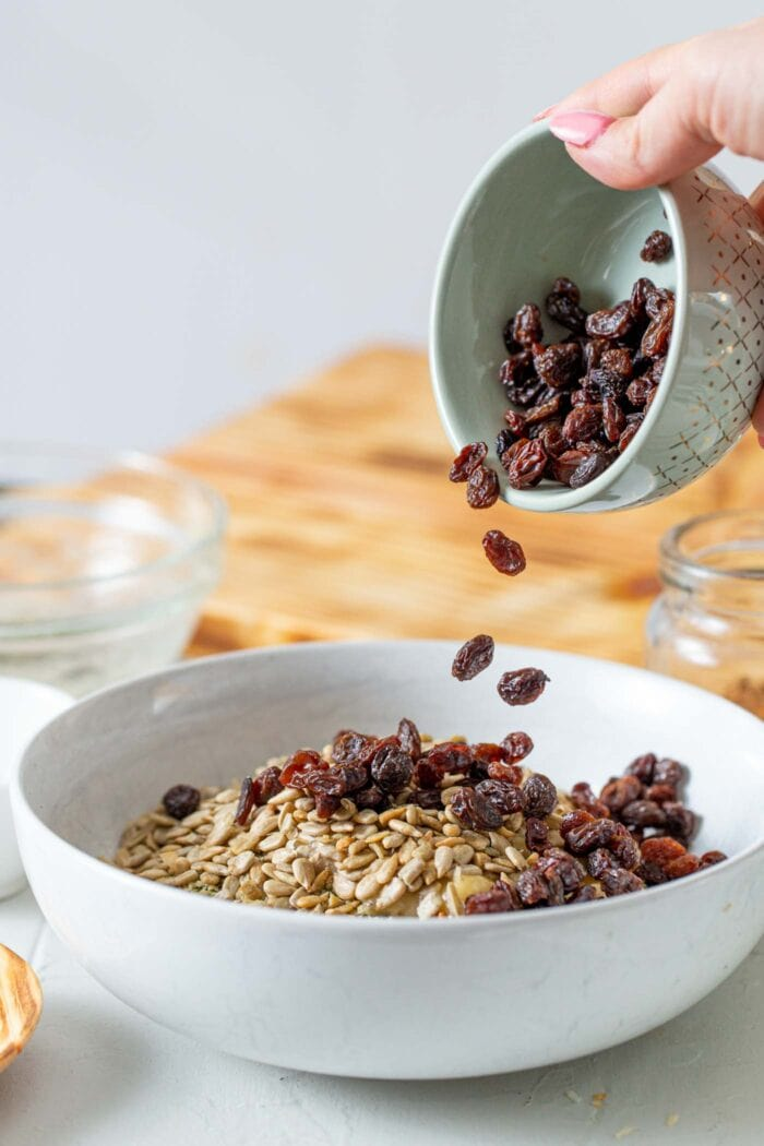 Adding raisins to a granola mixture in a large mixing bowl.
