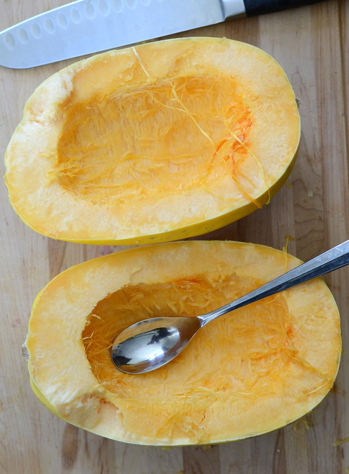 Spaghetti squash cut in half with a spoon to scoop out the seeds and a knife beside it.
