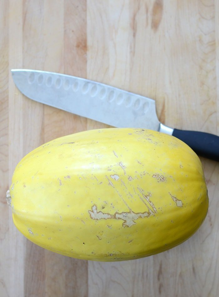 Spaghetti Squash on a cutting board with a large knife beside it.