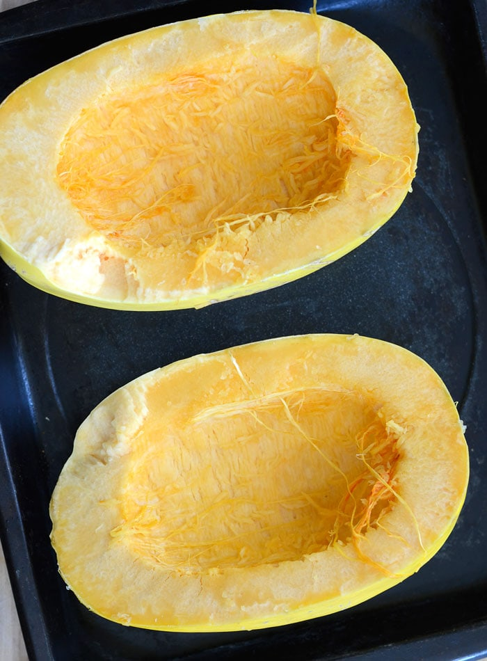 Cut spaghetti squash placed face up on a baking tray.