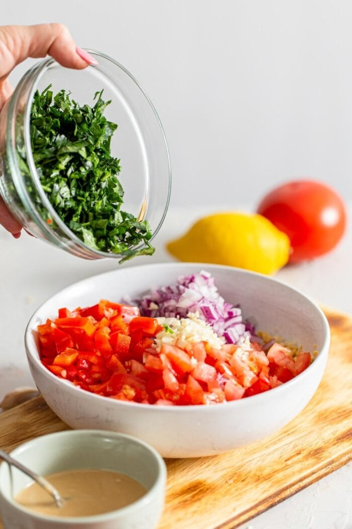 A bowl of chopped parsley being added to a bowl of fresh chopped veggies.