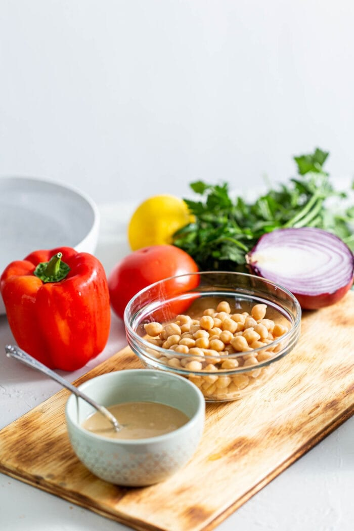 Chickpeas, tahini, bell pepper, onion, parsley and red onion on a cutting board.