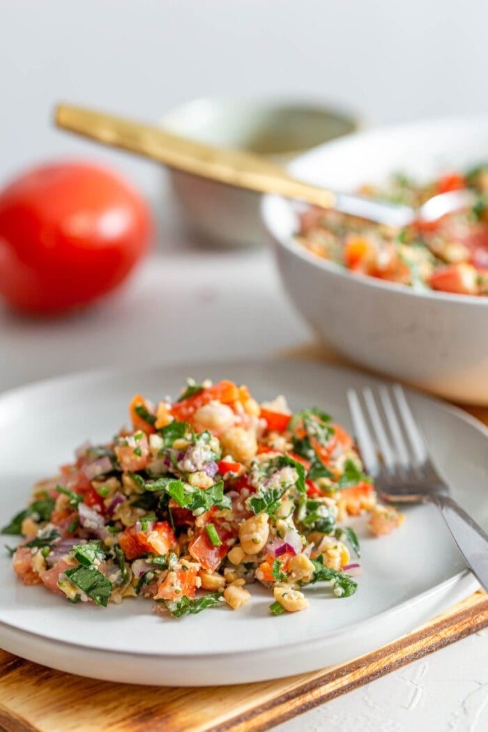 Chickpea tabouleh salad on a small plate with a fork.