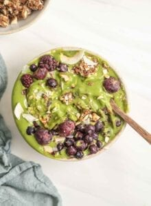 A thick green smoothie in a bowl topped with berries and nuts.