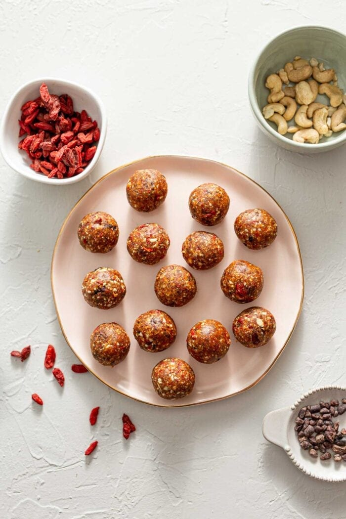 A plate of goji berry balls with containers of goji berries and cacoa nibs set around it.
