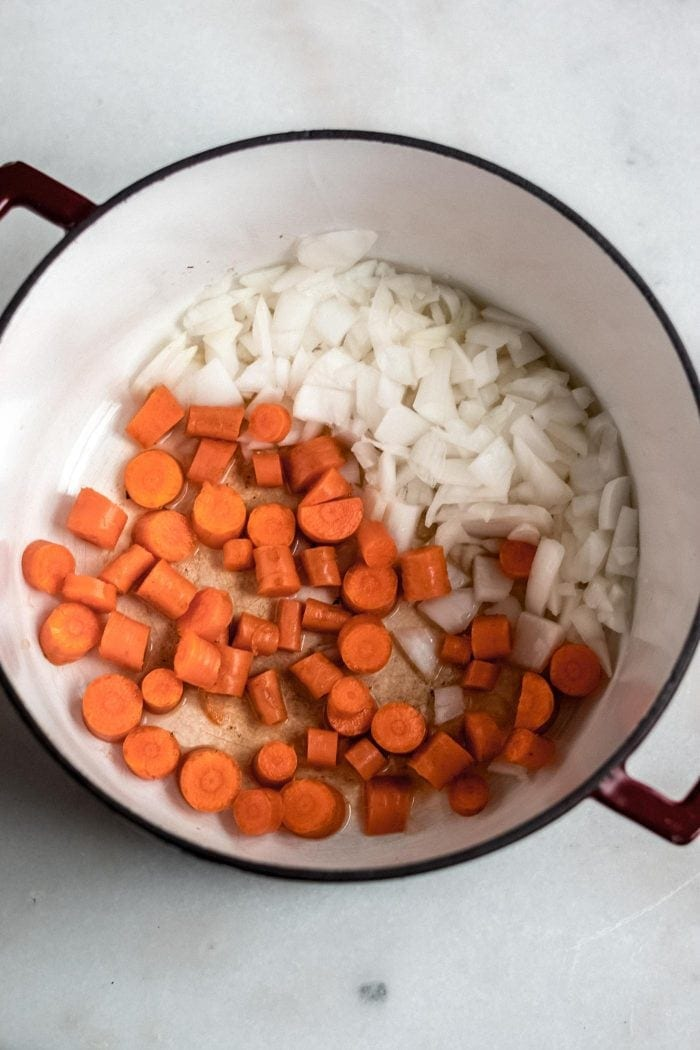 Carrots and onion in a soup pot.