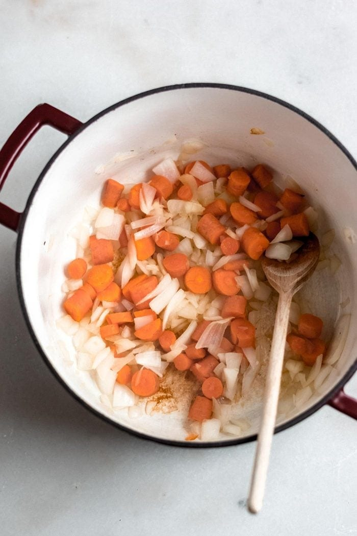 Carrots and onion in a soup pot with a wooden spoon.