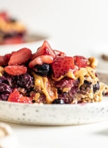 Baked oatmeal topped with berries on a plate with a spoon, two additional plates in background.