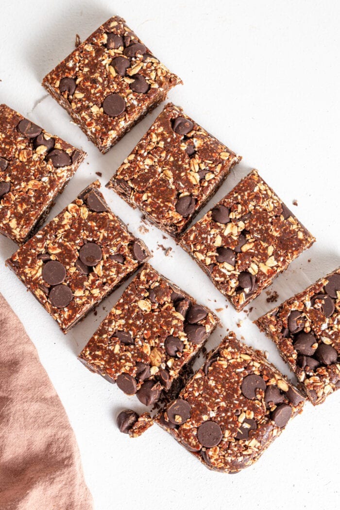 Overhead image of 8 chocolate date squares on a surface.