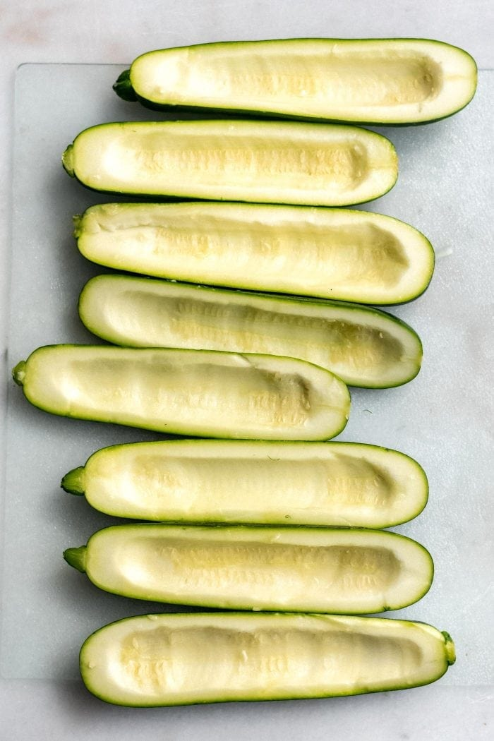 4 medium-sized zucchini with their seeds scooped out on a baking tray lined with parchment paper.
